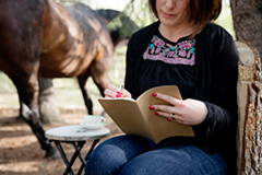 woman reading with horse in background