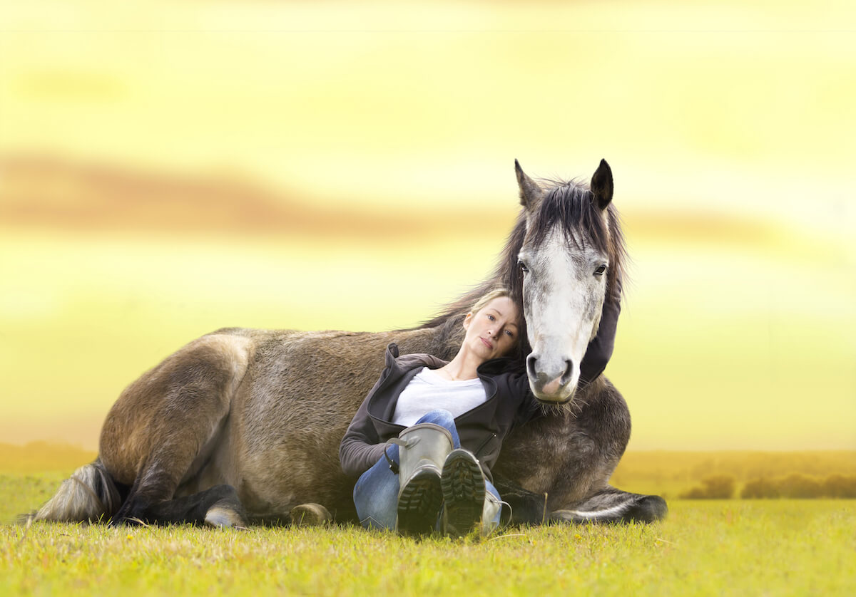 woman relaxing with horse on ground